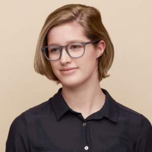 This is a lady with medium length blonde hair wearing a black blouse and modelling a pair of Espy and Iris glasses. The glasses are called Aish the colour is a matt blue. The material is acetate with a rounded square shape..
